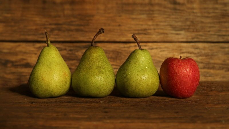 The red apple among the green pears