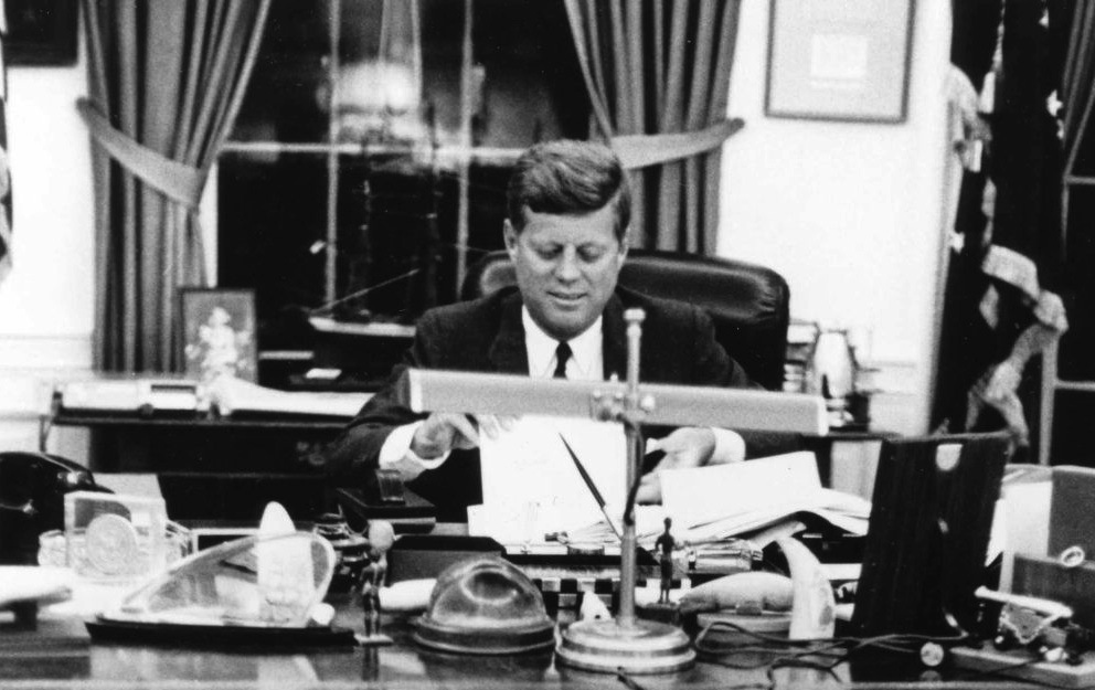John F Kennedy at his desk in the Oval Office