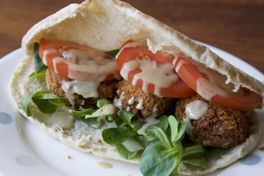 Easy Vegan Falafel Recipe. Chickpea falafel served in soft white pitta bread with salad leaves, tomato and tahini