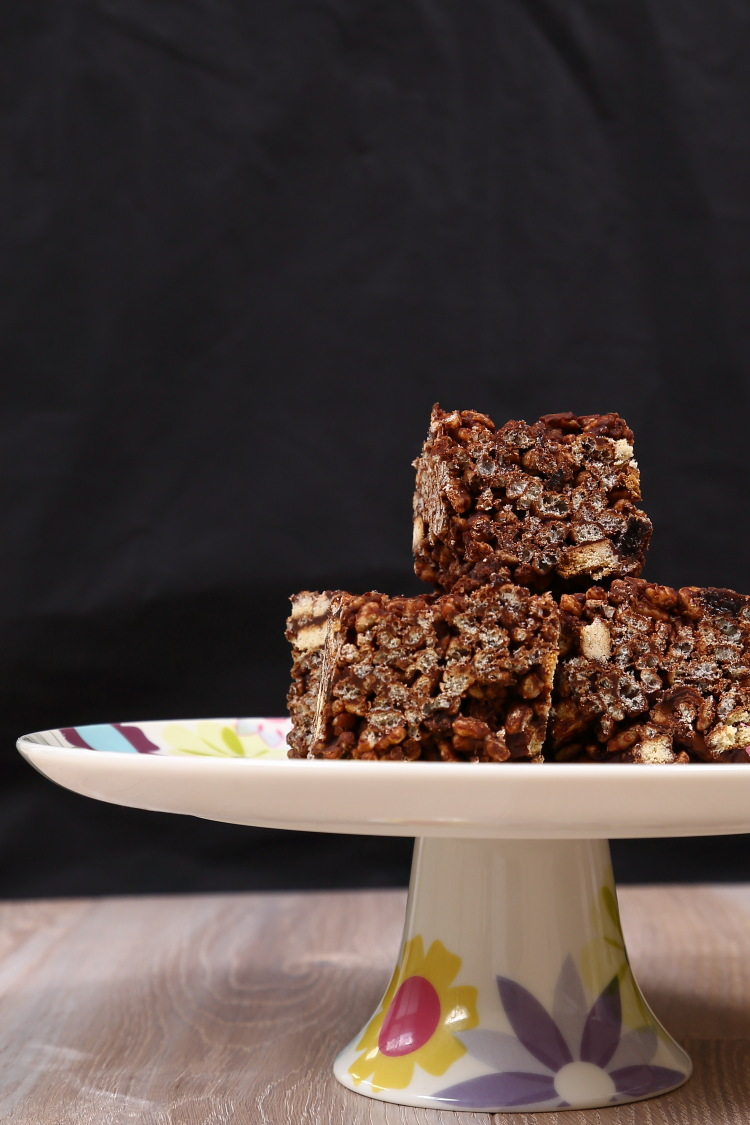 Chocolate Tiffin squares on a cake stand against a black background