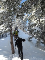 Climbing off piste to ski a bowl in Taos