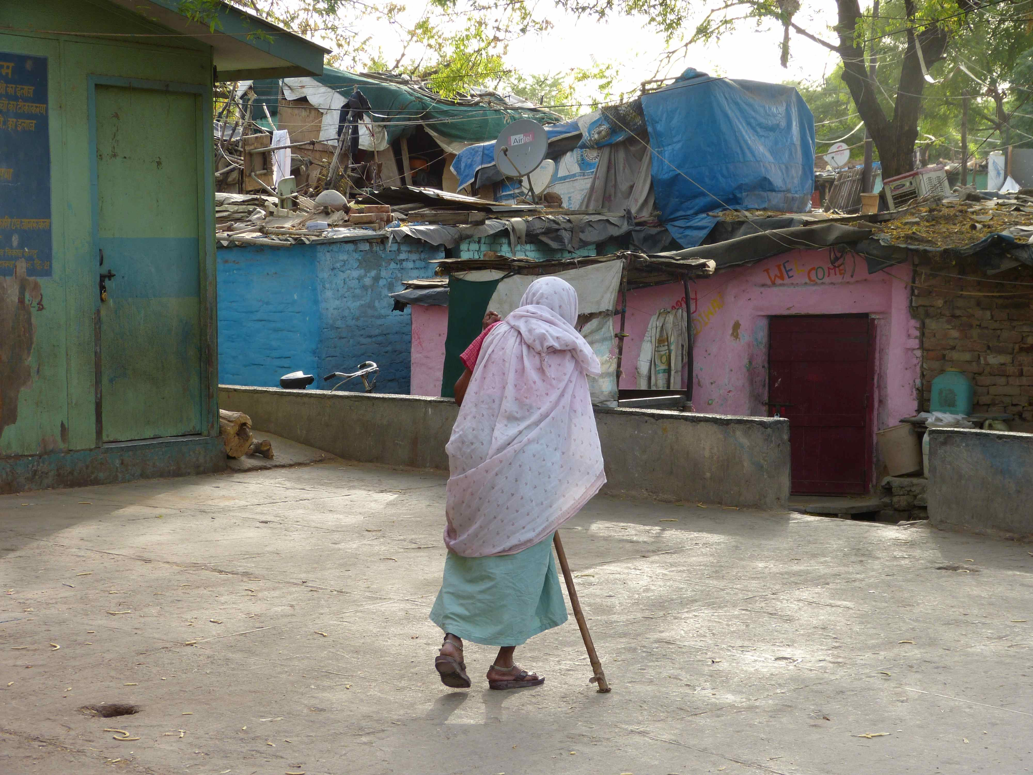 Old woman returning from public toilet for thousands in a Delhi slum