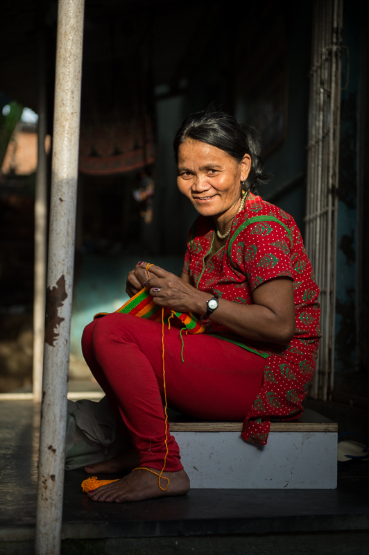 This photo captures a human trafficking survivor from Mumbai, India sewing a purse.  She still lives in the Red Light District to help other women through the Manna Prayer House.  TO THE MARKET buys from Manna Prayer House for our pop-up shops. Photo credit: Neil Ruskin.