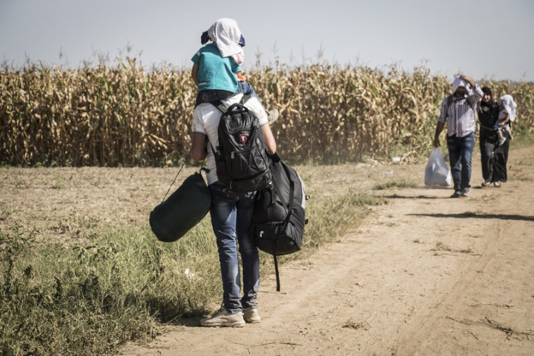 A man carrying his little boy on his shoulers, a backpack on his back, another backpack on one arm, and a bag in the other, waits for some people down the path towards Croatia. Photo credit: Stuart Sia/Save the Children