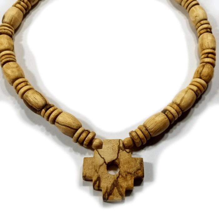 closeup of palo santo chakana design on a necklace