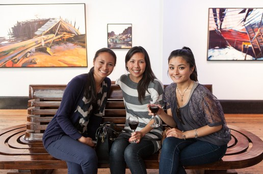 Visitors enjoy a glass of wine at a local gallery