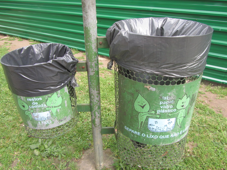 Different sized bins with 'familia folha' (leaf family) mascot, bus park, Curitiba