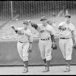 New York Yankees Myril Hoag, Ben Chapman, and Joe DiMaggio striking a throwing pose in front of the screen at Fenway Park.