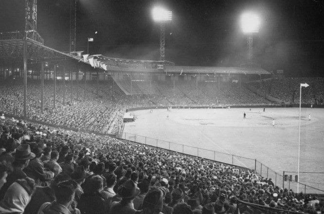 In front of the largest crowd in 13 years, the New York Giants defeat the Boston Braves, 5 – 1, in the first night game played at Braves Field. The 37,407 fans are surprised as their hometown heroes enter the field wearing shiny satin uniforms designed to reflect the light generated by the electricity used for the evening contest.