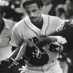 Jim Rice climbs into the Fenway Park stands from the dugout to assist a young boy who had just been hit in the head by a savage line drive foul off the bat of Dave Stapleton. The Red Sox slugger's quick response of picking up the four year-old boy and running through the dugout to a waiting ambulance is credited with possibly saving the child's life.