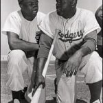 Frank Robinson (left), a Cincinnati Redlegs (Reds) rookie, and Jackie Robinson of the Brooklyn Dodgers share a moment prior to a 1956 exhibition game in Florida.