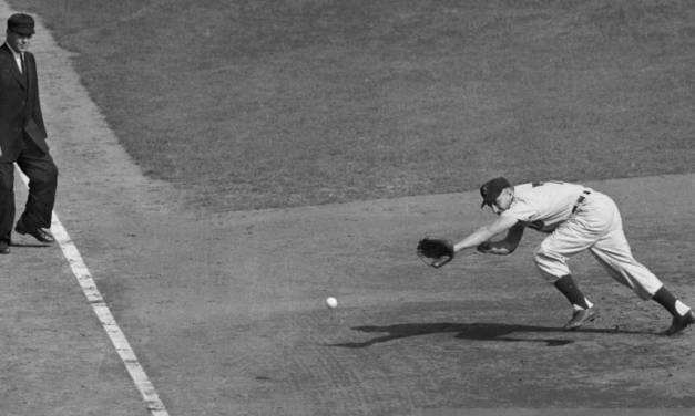 Al Rosen of the Cleveland Indians is doing a mighty stretch in an attempt to reach the ball as Wes Westrum