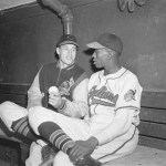 Bob Feller and Satchel Paige chat in the dugout before the game with the White Sox in Cleveland