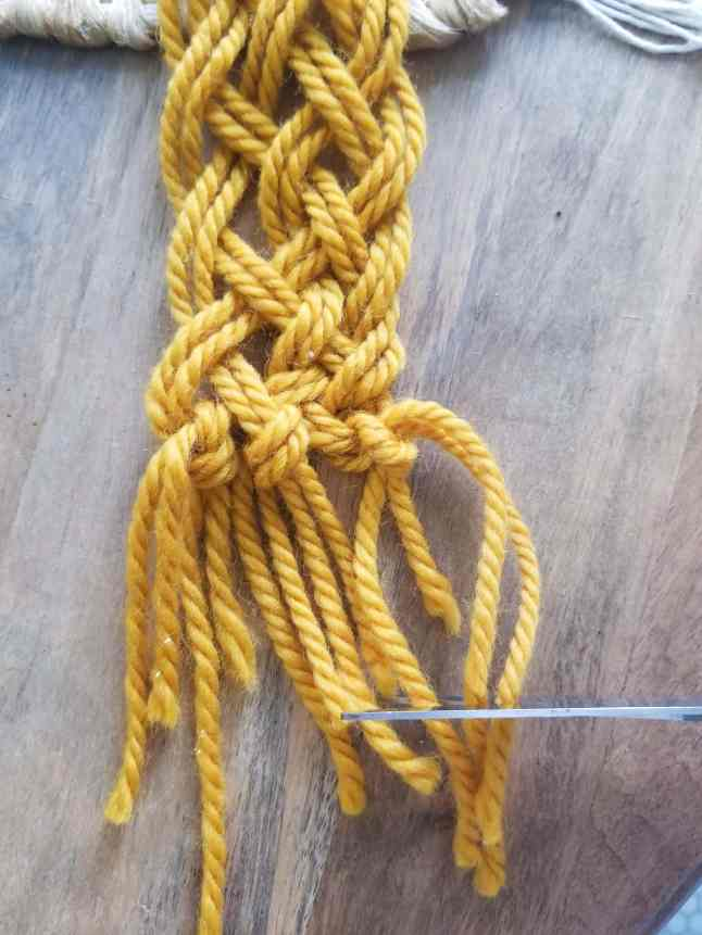 yellow yarn macrame project knotted ends.