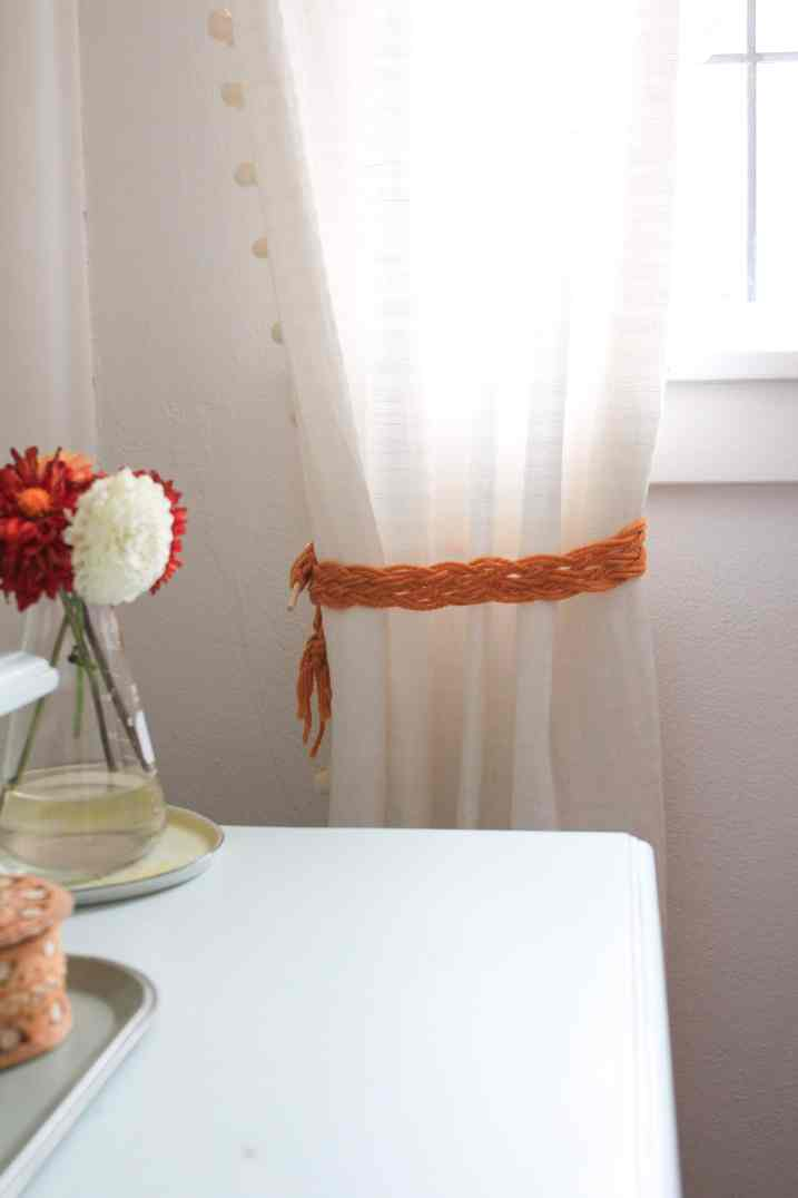White curtain tied back with a yellow macrame tie back.