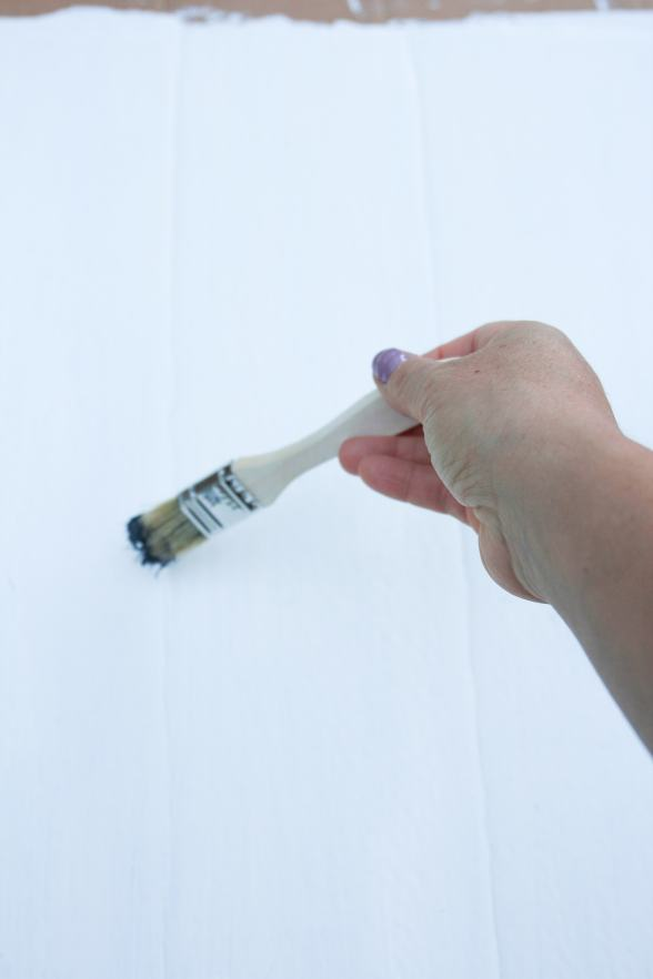 Hand holding paint brush dipped in navy blue paint.