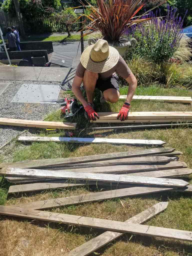 Man holding 2x4's to make diy privacy screen.