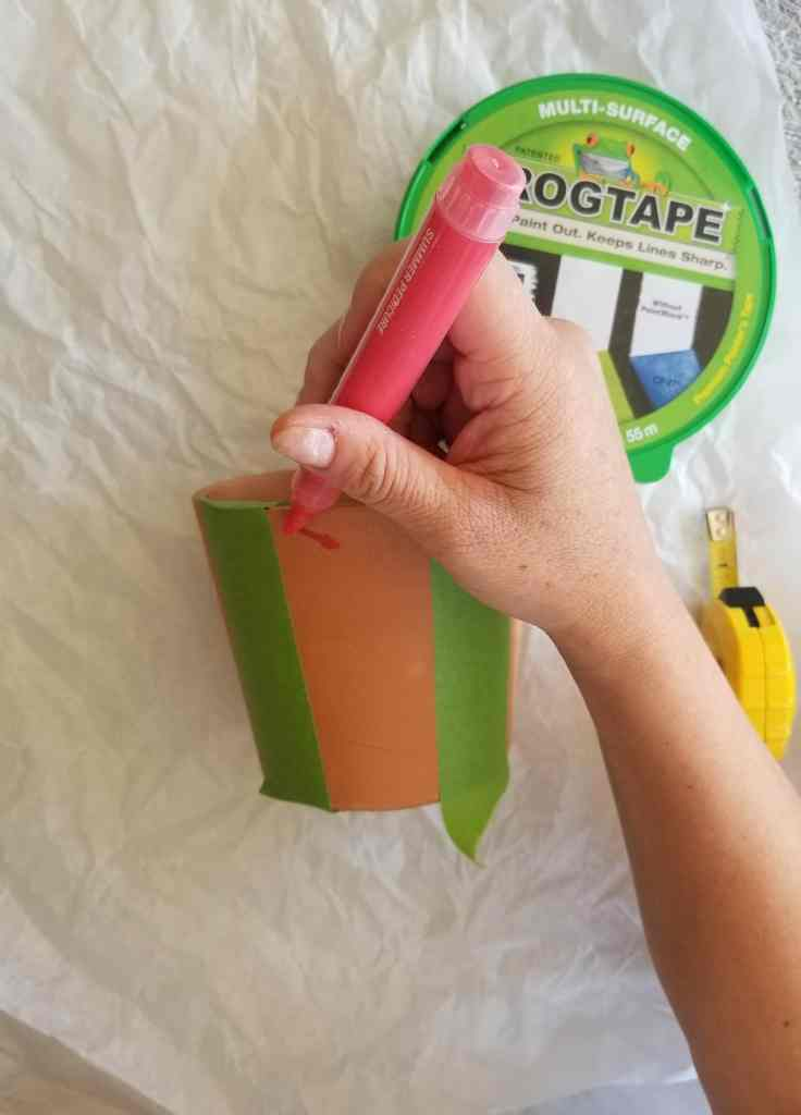 Hand holding paint marker painting on terra cotta pot.
