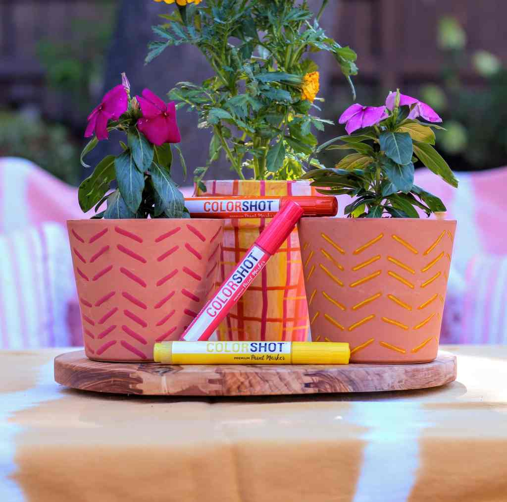 Three  terra cotta Flower pots  painted with paint markers in modern chevron pattern. Colorshot paint markers leaning on pots.