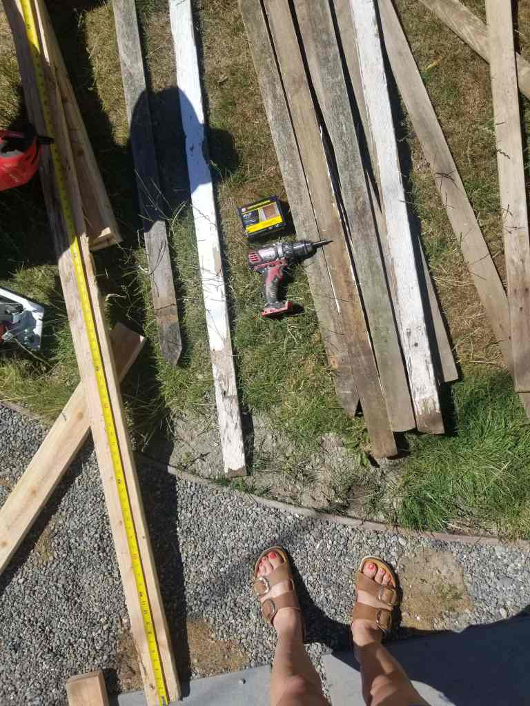 Deconstructed picket fence on ground with tools.