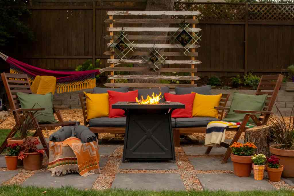 Outdoor fall scene with black fire pit table. Wood patio furniture with throw pillows in red, yellow and green. Potted plants, throw blankets and hammock. Privacy screen with hanging planters.