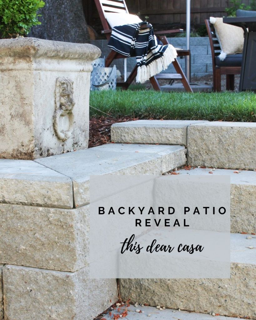 backyard retaining wall and steps leading up to patio. square concrete planter with lion detail.