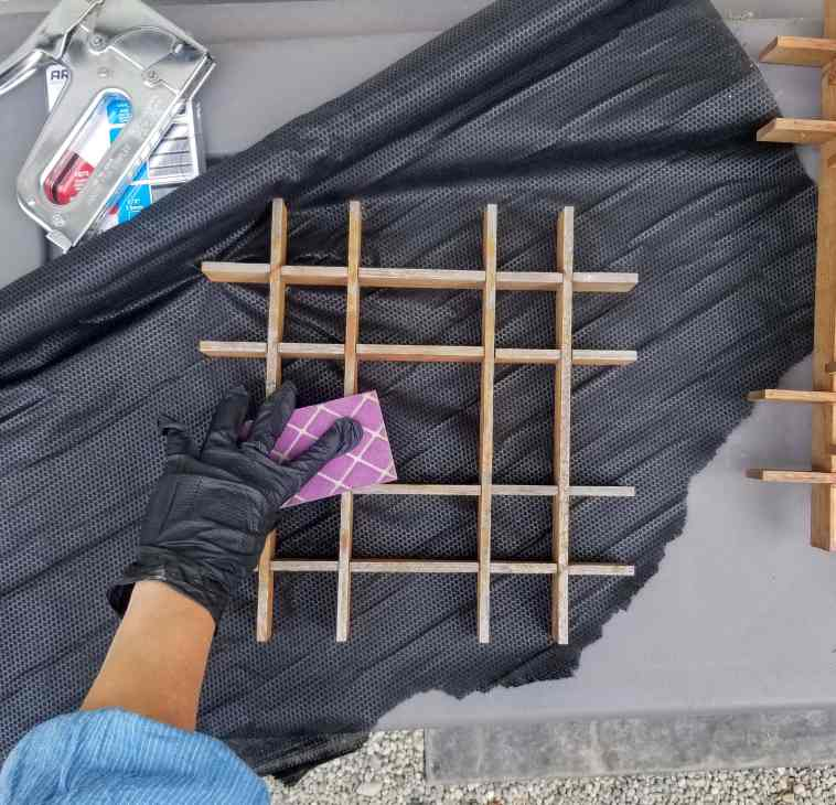 Person's hand in glove using sanding block on wood structure for a diy living gallery wall.