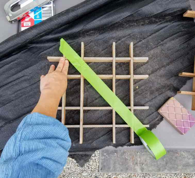Person's hand taping off wood structure for diy living gallery wall.