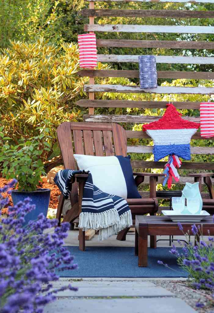 Brown wood adriondack chair with classic navy and white throw pillow. Privacy screen with patriotic lanterns. Pitcher and drinks on table.