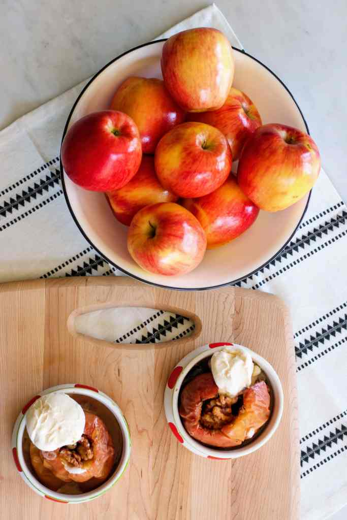 White bowl full of apples next to wood cutting board. Two Baked apples topped with vanilla ice cream.