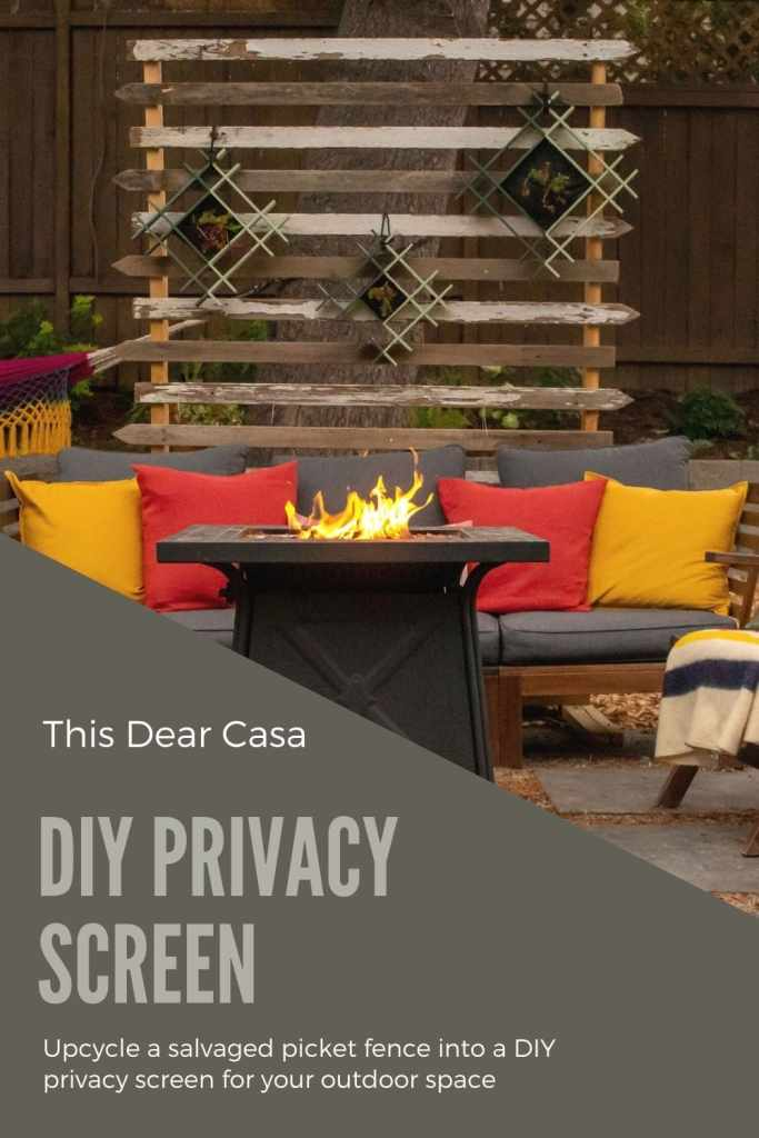 DIY privacy screen with planters hanging on it. Outdoor sofa in front of screen and fire pit table lit.