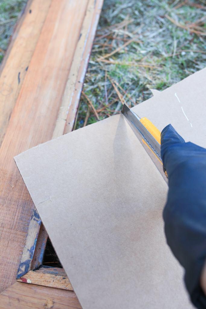 Hand cutting cardboard with box cutter.
