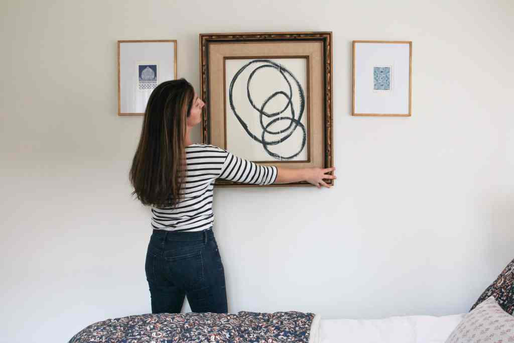 Woman hanging framed abstract art on wall.