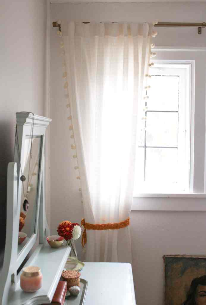Bedroom window with cream color curtains and yellow diy macrame tie back.