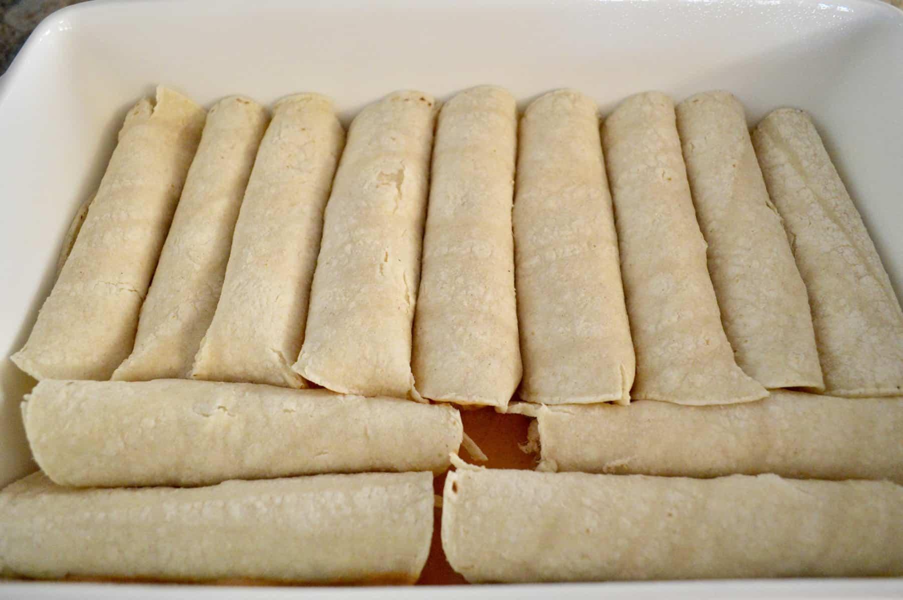 rolled enchiladas in a baking pan of sauce for cream cheese chicken enchiladas