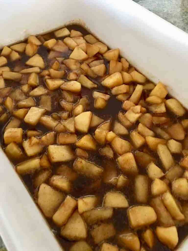 apples and cinnamon mixture at the bottom of white baking pan