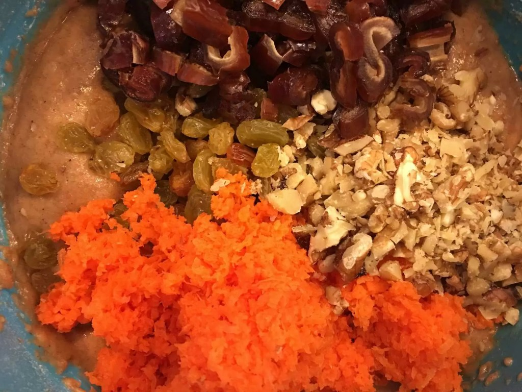 Batter for healthy carrot muffins including shredded carrots, chopped dates, raisins, and walnuts