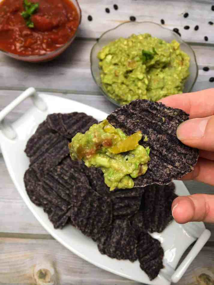 holding black bean chip with guacamole