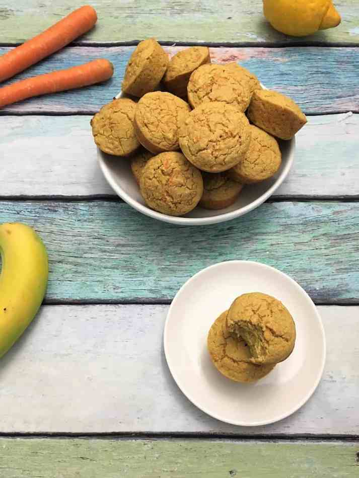 carrot cake muffins in bowl with a bite from one muffin in plate