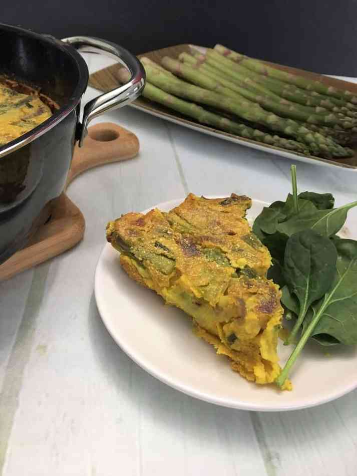 vegan asparagus frittata slice on plate with spinach salad
