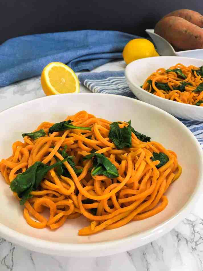 plate of cooked sweet potato noodles and spinach on blue towel