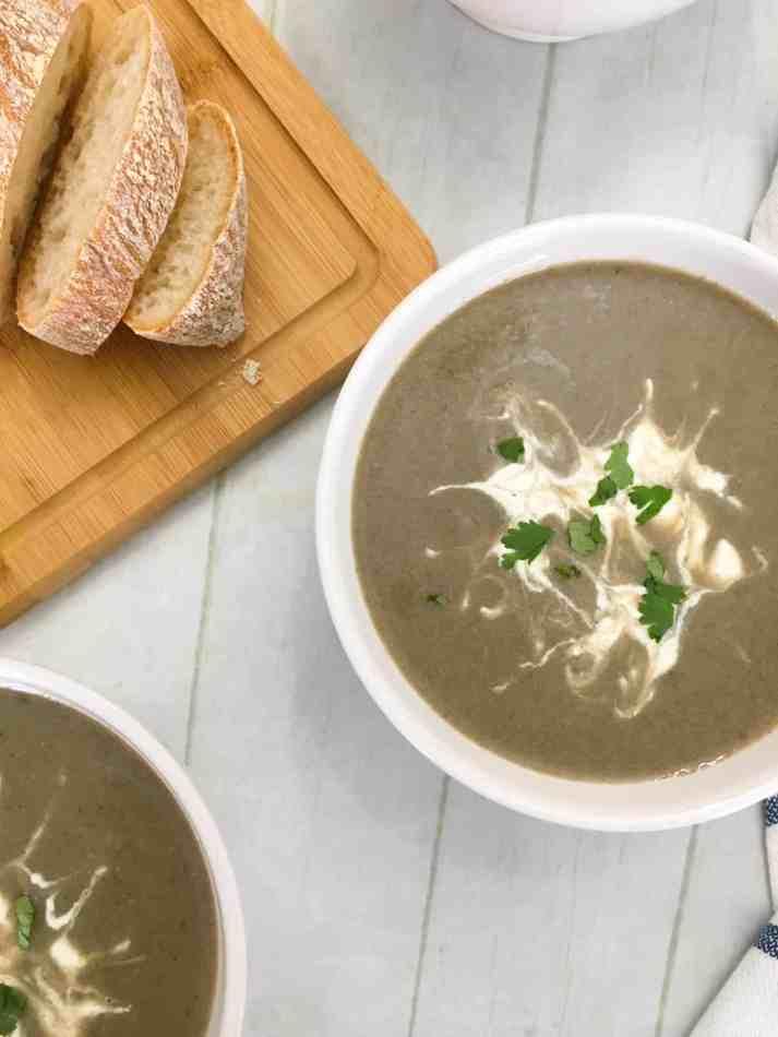 vegan mushroom soup in bowl with cashew cream and parsley garnish