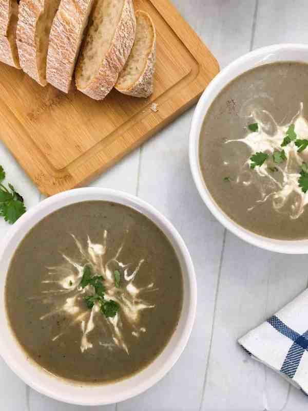 vegan mushroom soup with cashew cream garnish and sliced bread in background