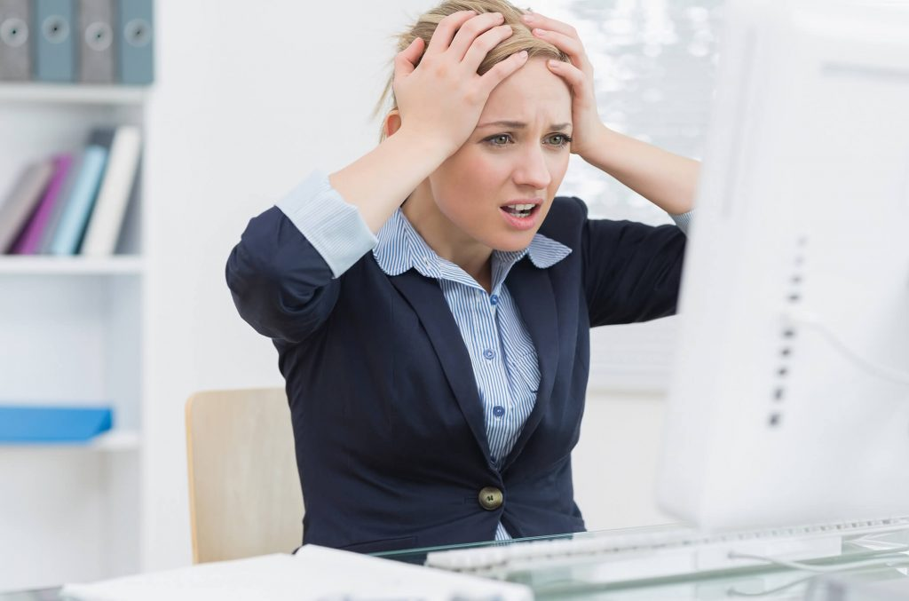 A frustrated looking woman looking at her computer