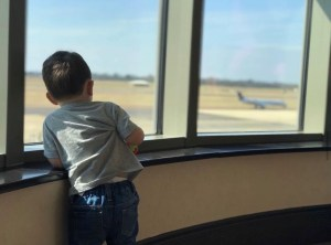 A little boy watches airplanes at an airport while waiting on his international flight.