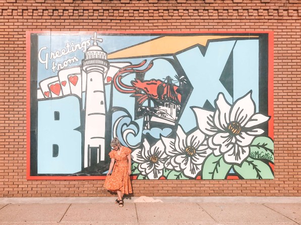 A young woman in a floral dress stands in front of a mural in downtown Biloxi.