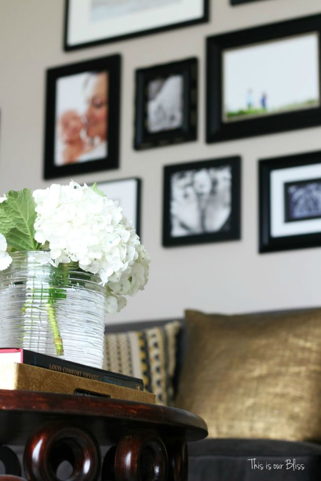 How to style a coffee table - coffee table styling - elements of a well-styled coffee table - Living room couch -black frame gallery wall - gold pillows - Back to Basics - This is our Bliss