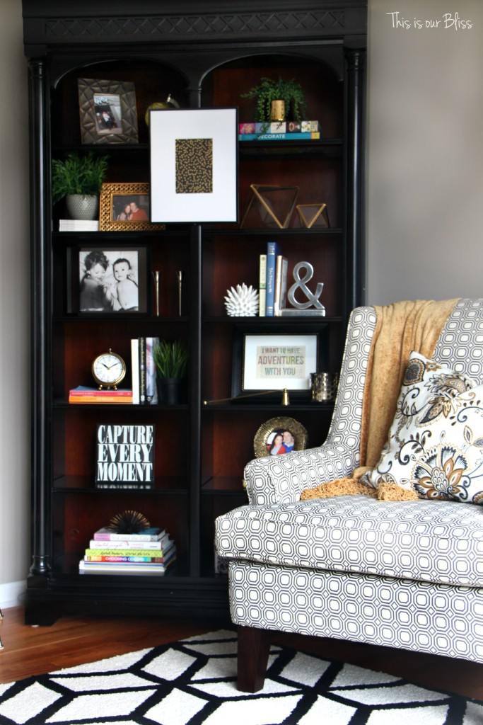 how to update an old bookcase with command hooks - 30 second makeover - formal living room bookcase - hanging art on a bookcase - living room chair - bookcase after - This is our bliss