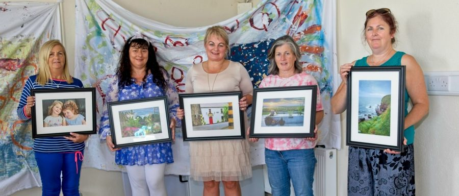 Participants showcasing their framed photographs after the Carbally Photography course.