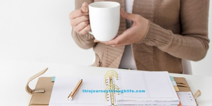 Woman holding coffee mug, in front of calendar/planner and pen